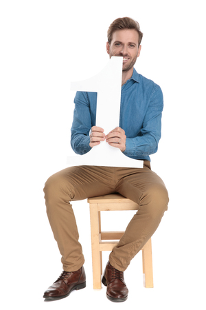 Hopeful man holding tight a number one maquette while smiling and wearing a blue shirt and brown pants, sitting on a chair on white studio background Banco de Imagens - 124457003