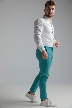 Unimpressed man stepping to the side and looking over his shoulder while wearing a white shirt and jeans on gray studio background