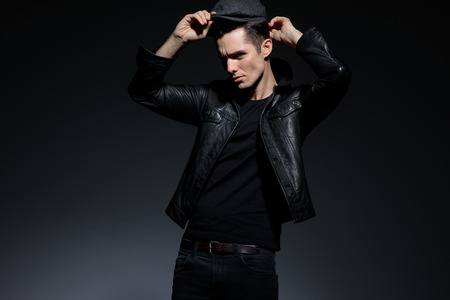 Artistic guy putting on his cap and confidently looking forward while wearing a black leather jacket and a pair of black jeans, standing on gray studio background