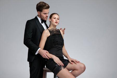 Apuesto joven vestido con un esmoquin de pie y abrazando a su novia por detrás mientras ella está sentada en una silla con los brazos en las piernas sobre fondo gris de estudio