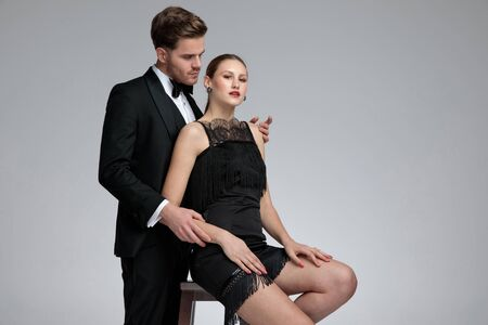 Handsome young man dressed in a tuxedo standing and embracing his girlfriend from behind while she is sitting on chair with her arms on her legs on gray studio background