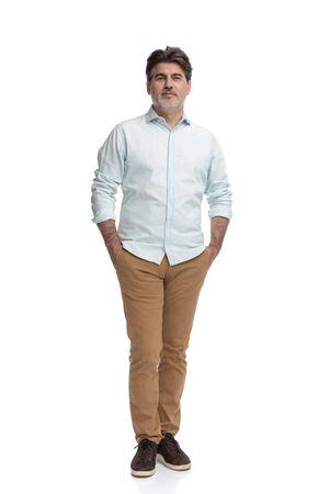 Lässiger alter Mann, der mit beiden Händen in den Taschen steht, während er ein weißes Hemd und eine braune Hose auf weißem Studiohintergrund trägt