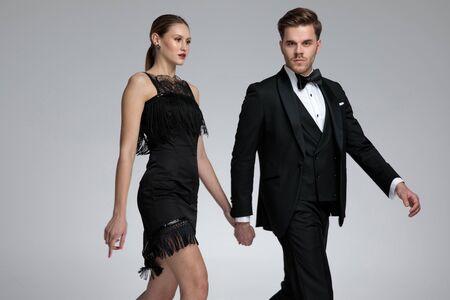 Ernsthaft aussehendes Paar, das Händchen hält und zur Seite tritt, während er selbstbewusst in die Kamera schaut und einen Smoking auf grauem Studiohintergrund trägt Standard-Bild