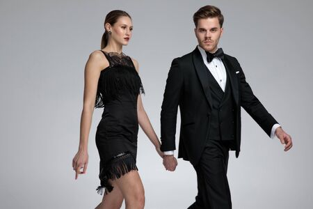 Serious looking couple holding hands and stepping to the side while he is confidently looking to the camera and wearing a tuxedo on gray studio background Banco de Imagens
