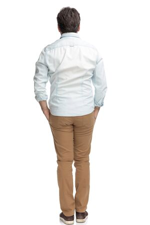 Rear view of casual old man standing with his hand in his pockets while wearing brown pants and a white shirt on white studio background