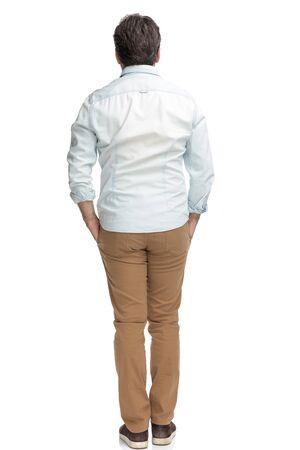 Vista trasera del anciano casual de pie con la mano en los bolsillos mientras usa pantalones marrones y una camisa blanca sobre fondo blanco de estudio