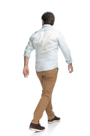 Confident casual man walking forward while wearing brown pants and white shirt on white studio background
