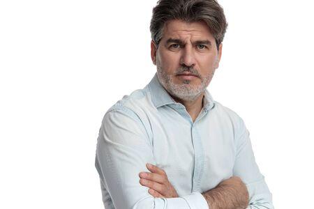 Cerca del anciano molesto frunciendo el ceño a la cámara y sosteniendo sus brazos cruzados sobre su pecho mientras usa una camisa blanca y está de pie sobre fondo blanco de estudio