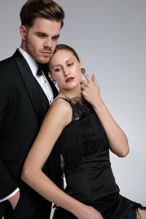 Handsome groom standing and holding his hand in his pocket while his girlfriend is touching her neck and leaning on him on gray studio background