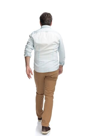 Determined casual man walking forward hurried while wearing a white shirt on white studio background Stock Photo