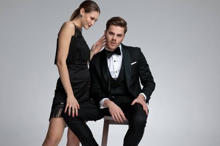 Confident young groom sitting wearing a tuxedo while being comforted by his girlfriend standing beside him on gray studio background Standard-Bild