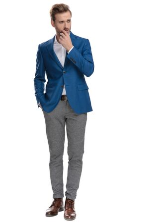 Eager casual man holding his hand in his pocket and on his chin while looking curiously to the side and wearing a suit, standing on white studio background