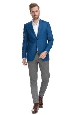 Serious looking casual man confidently walking forward while wearing an elegant suit on white studio background