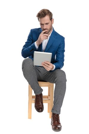 Concerned casual man reading on his tablet and holding his hand on his chin while sitting on a chair and wearing a suit on white studio background