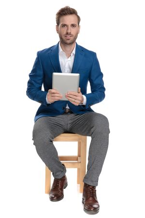 Confident casual man holding his tablet and looking forward while wearing an elegant suit and sitting on a chair on white studio background 版權商用圖片