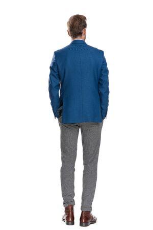 Vista posterior de un hombre casual pensativo mirando a otro lado y sosteniendo su mano en los bolsillos mientras usa un traje y está de pie sobre fondo blanco de estudio