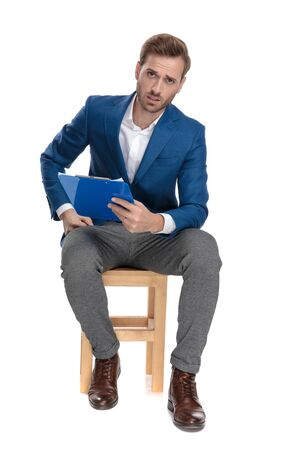 Upset casual man holding a clipboard and frowning while wearing a suit and sitting on a chair on white studio background 版權商用圖片