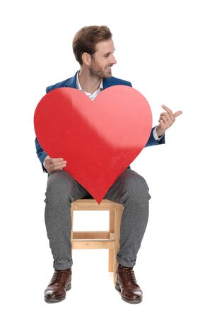 Confident casual man pointing to a heart shape that he is holding while smiling and wearing a suit, sitting on a chair on white studio background