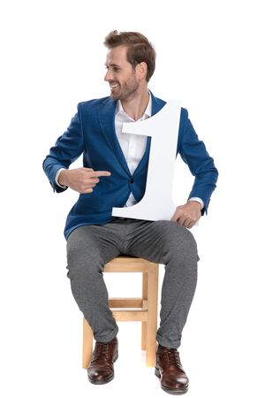 Young casual man pointing to a number one that he is holding on his lap while wearing a suit and sitting on white studio background 免版税图像