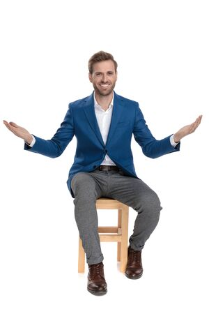Positive casual guy sitting with his hands wide open while wearing a suit and smiling on white studio background