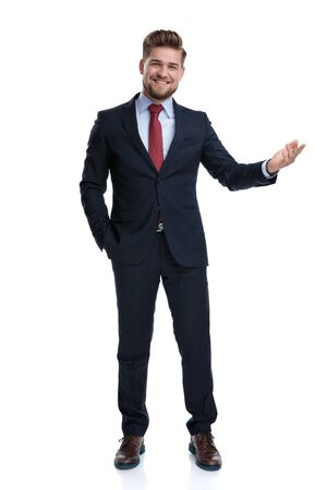 Cheerful businessman presenting with his hand in his pocket while laughing and wearing a blue suit, standing on white studio background 免版税图像 - 126563014