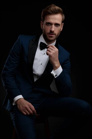 Mysterious groom sitting and leaning on his leg while wearing an elegant blue tuxedo and posing on black studio background Stock Photo
