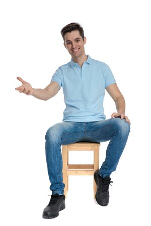 Joyful casual guy greeting and smiling while wearing a blue shirt and jeans, sitting on a chair on white studio background