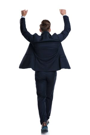Back view of a celebrating businessman stepping forward and holding both hands in the air while wearing a blue suit on white studio background