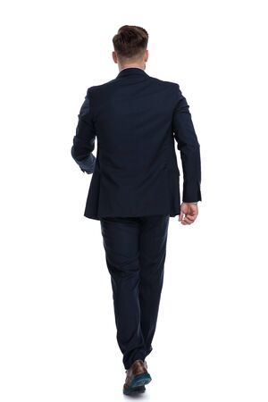 Rückansicht eines wandelnden Geschäftsmannes in einem blauen Anzug auf weißem Studiohintergrund