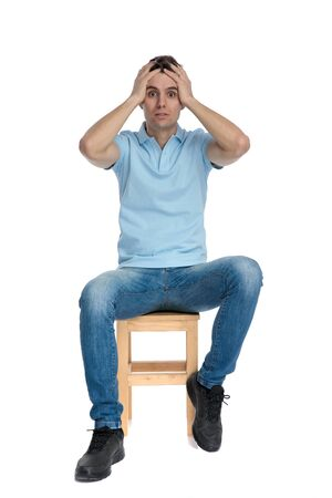 Nervous casual guy holding his hands on his head and looking forward frightened while wearing a blue t-shirt and jeans, sitting on white studio background