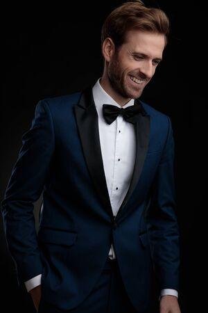 Jeune homme positif riant tout en tenant sa main dans sa poche et en regardant vers le bas, vêtu d'un smoking bleu en se tenant debout sur fond de studio noir