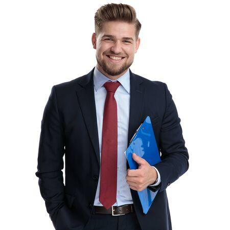 Lustiger Geschäftsmann lacht und hält eine Zwischenablage, während er seine Hand in der Tasche hält und einen blauen Anzug trägt, der auf weißem Studiohintergrund steht