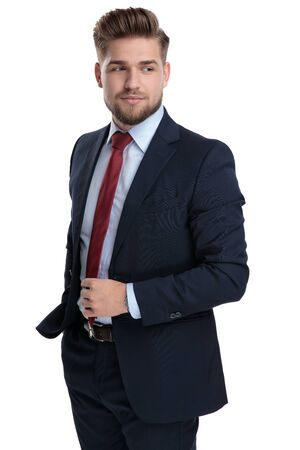 Determined businessman adjusting his tie and holding his hand in his pocket while wearing a blue suit and standing on white studio background Stockfoto