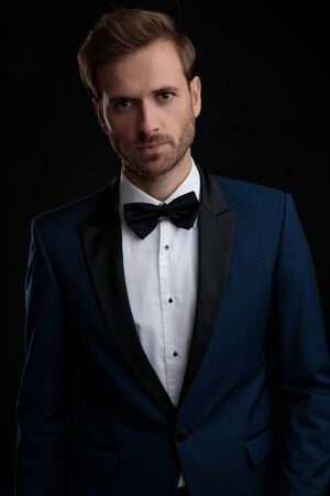 Serious looking groom posing while wearing a blue tuxedo and a black bowtie, standing and posing on black studio background