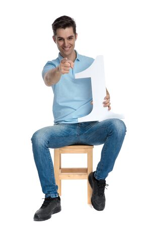 Positive casual guy pointing and holding a number one while smiling and wearing a blue shirt, sitting on a chair on white studio background