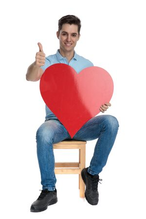 Succesful casual guy holding a heart shape and gesturing ok while smiling and wearing jeans, sitting on a chair on white studio background