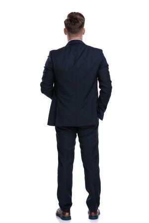 Vista posterior de un joven empresario sosteniendo su mano en el bolsillo mientras usa un traje azul y de pie sobre fondo blanco de estudio Foto de archivo