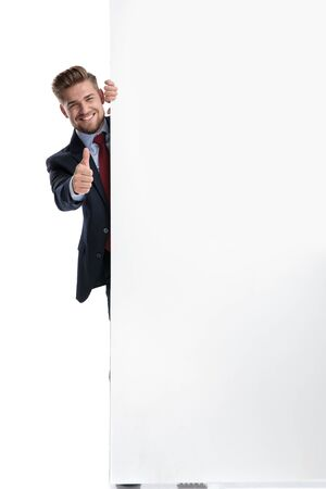 Happy businessman gesturing ok from behind a blank billboard while wearing a blue suit and standing on white studio background Banque d'images