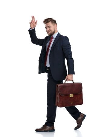 Handsome businessman greeting and holding his briefcase while stepping and wearing a blue suit on white studio background Stock Photo