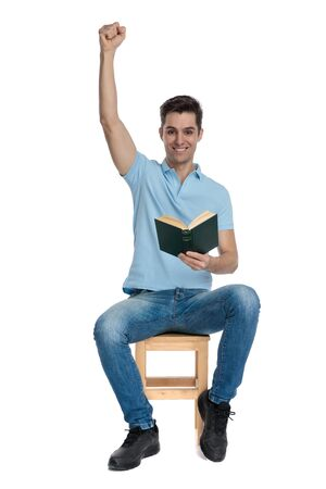 Happy casual man celebrating with his fist in the air and holding a book while smiling and sitting on a chair on white studio background