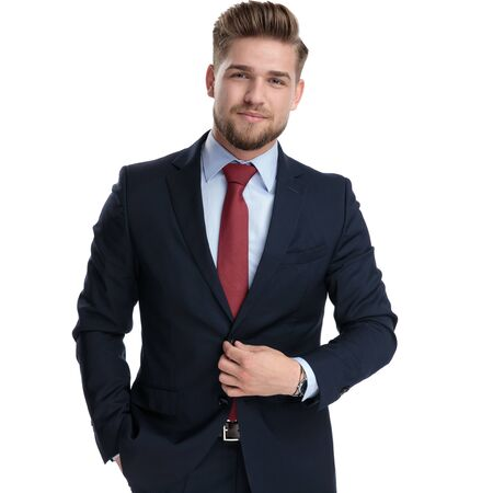 Determined businessman unbuttoning his jacket and holding his hand in his pocket while wearing a blue suit and standing on white studio background