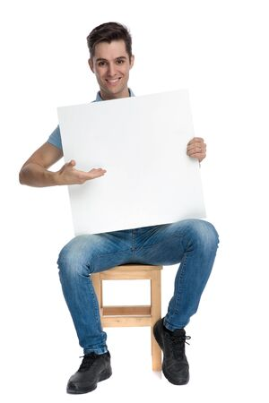 Cheerful casual guy presenting and empty billboard while smiling and wearing blue jeans, sitting on a chair on white studio backgorund