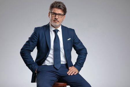 Hombre de negocios de aspecto serio sosteniendo su mano en el bolsillo mientras usa un traje azul y está sentado en un taburete sobre fondo gris de estudio