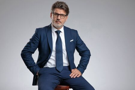Uomo d'affari dall'aspetto serio che tiene la mano in tasca mentre indossa un abito blu e si siede su uno sgabello su sfondo grigio studio