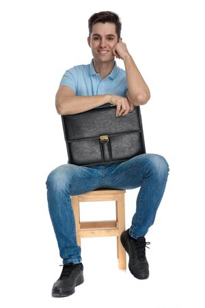 Happy businessman smiling and holding his suitcase while wearing blue jeans and sitting on a chair on white studio background 스톡 콘텐츠