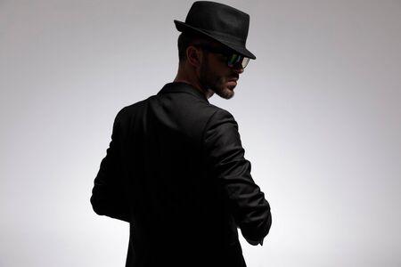 Achteraanzicht van een mysterieuze casual man met een bril, een zwarte hoed en een jas terwijl hij over zijn schouder kijkt en op een grijze studioachtergrond staat