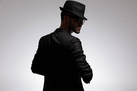 Back view of a mysterious casual man wearing glasses, a black hat and jacket while looking over his shoulder and standing on gray studio background Stock fotó