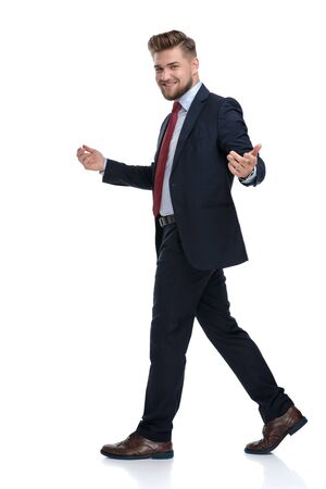 Happy businessman walking to the side and inviting while wearing an elegant blue suit on white studio background