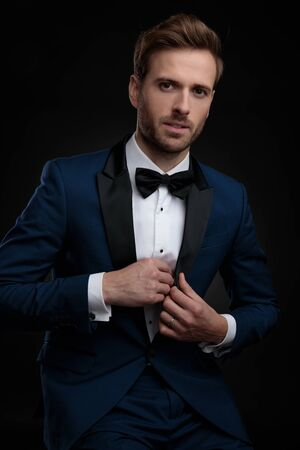 Confident young man about to take out a surprise from his blue tuxedo while sitting on black studio background