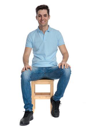 Beau mec décontracté portant une chemise bleue et un jean posant et assis sur une chaise sur fond de studio blanc
